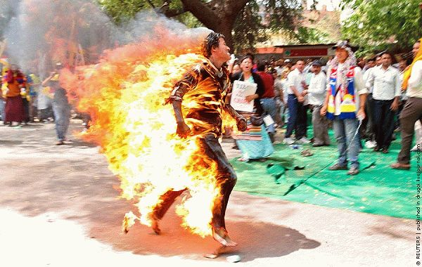 A Tibetan exile runs after setting himself on fire during a protest against the upcoming visit of Chinese President Hu in New Delhi