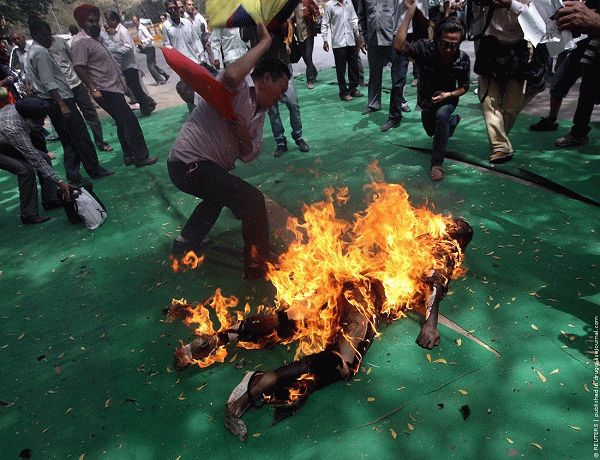 Tibetan exiles try to douse the flames from their comrade after he set himself on fire during a protest in New Delhi