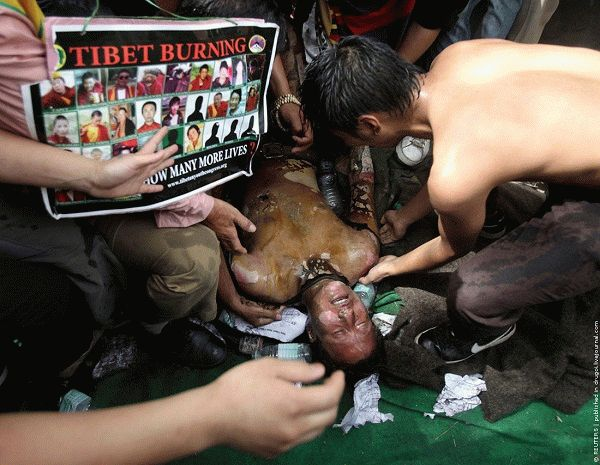 Tibetan exiles attend to their comrade after he set himself on fire during a protest in New Delhi