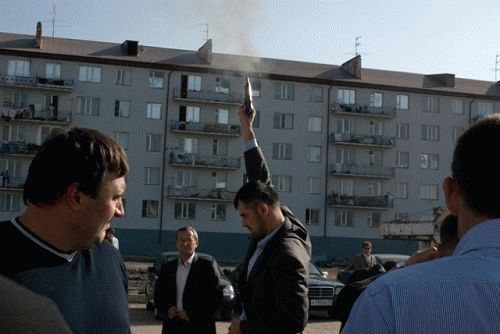 Men are shooting in the air celebrating the upcoming bride's car at a posh wedding party in downtown Grozny